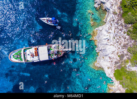 People swimming in the clear blue waters of Antipaxos Island, near Corfu - Kerkyra, Greece. Daily boat trips to - Stock Photo