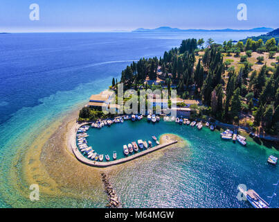 Kouloura old fishing village and beach. Corfu (Kerkyra) Island, Greece, Europe. Fishing boats and clear blue waters. - Stock Photo