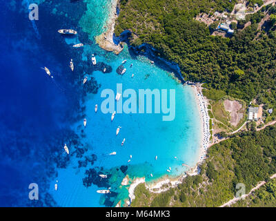 Antipaxos Island, Greece, with sandy beach, people swimming and yachts docked in the ethereal clear blue waters - Stock Photo