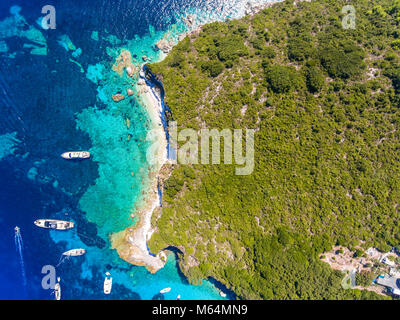 Antipaxos Island, Greece, with sandy beach, yachts docked in the ethereal clear blue waters of the Ioanian island - Stock Photo