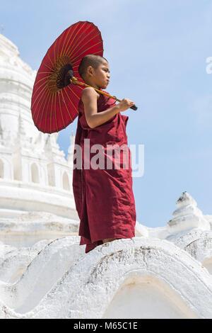 Young novice Buddhist monk holding parasol at Myatheindan Pagoda (also known as Hsinbyume Pagoda), Mingun, Myanmar - Stock Photo