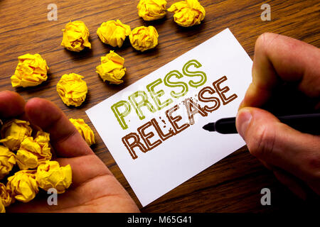 Word, writing Press Release. Concept for Statement Announcement Message written on notebook note paper on wooden - Stock Photo