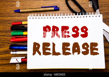 Word, writing Press Release. Business concept for Statement Announcement Message Written on notebook, wooden background - Stock Photo