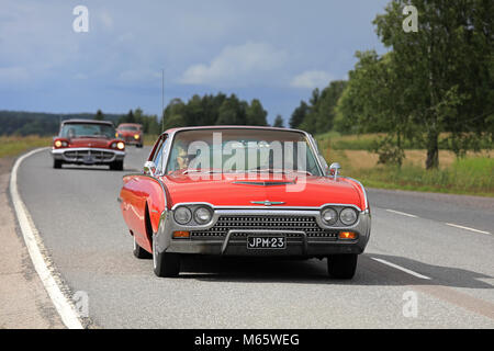 SOMERO, FINLAND - AUGUST 5, 2017: Red third generation (1961-1963) Ford Thunderbird classic car moves along rural - Stock Photo