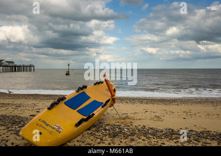 Southwold, England. A view from the beach looking out towards the sea.  A lifeguard's surfboard, from the RNLI, - Stock Photo