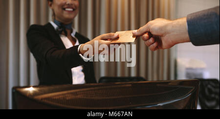 Close up of businessman paying with credit card at reception desk in hotel. Business man giving credit card to hotel - Stock Photo