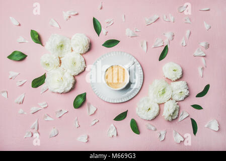 Cup of coffee surrounded with white ranunculus flowers and petals - Stock Photo