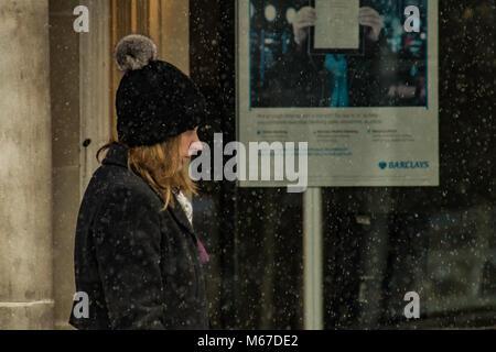 Leominster, UK. 1st Mar, 2018. UK Weather: A woman wearing a fur effect lined hood walks down Broad Street in Leominster - Stock Photo