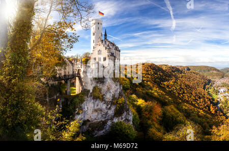 romantic lichtenstein castle germany baden wuerttemberg in autumn colours blue sky and clouds panoramic view - Stock Photo