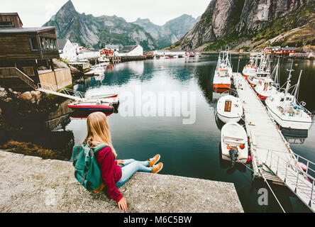 Young woman tourist relaxing on bridge over fjord in Lofoten islands of Norway Travel backpacking lifestyle concept - Stock Photo