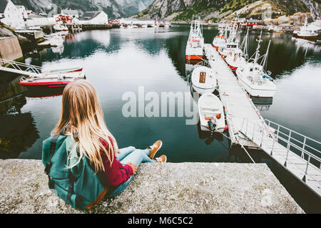 Blonde woman with backpack relaxing on bridge over sea with boats view Travel lifestyle concept adventure outdoor - Stock Photo