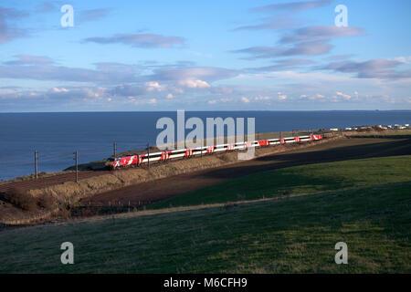 A Virgin Trains east coast class 91 + Intercity 225 train passes Marshall meadows, (north of Berwick upon Tweed) - Stock Photo