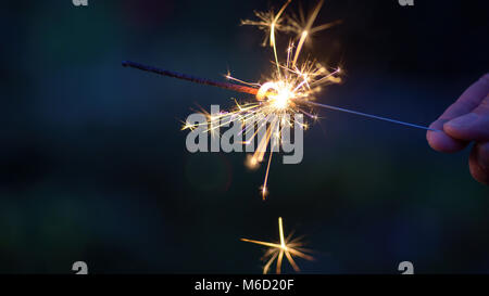 macro closeup of a person holding a sparkler outside in dark - Stock Photo