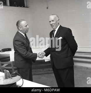 1960s, England, UK, picture shows two well-dressed men wearing suits standing up shaking hands. A firm handshake - Stock Photo