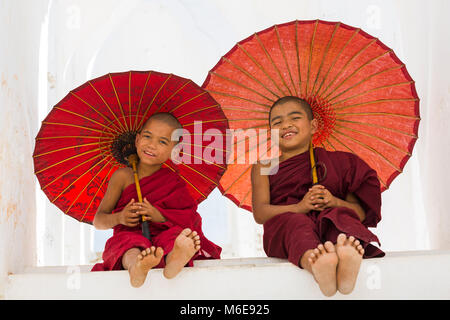 Young novice Buddhist monks holding parasols at Myatheindan Pagoda (also known as Hsinbyume Pagoda), Mingun, Myanmar - Stock Photo