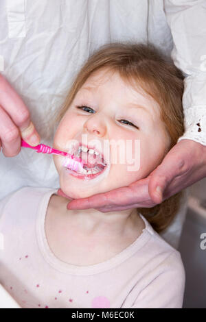Three year old child / kid aged 3 years having her milk teeth brushed with a toothbrush / tooth brush - by her mother - Stock Photo