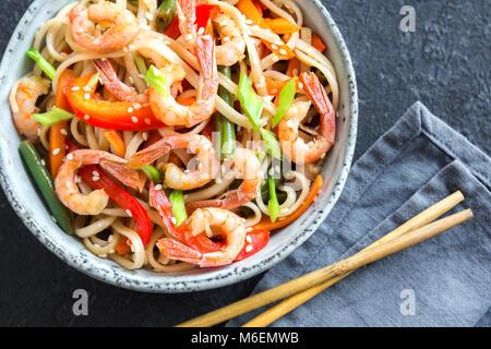 Stir fry with udon noodles, shrimps (prawns) and vegetables. Asian healthy food, meal, stir fry in bowl over black - Stock Photo