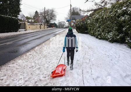 A boy walks on a journey alone on the snow covered path pulling a sledge alongside the A36 towards the Red Rover - Stock Photo