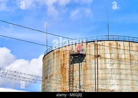 Old tanks for storage of waste oil on a blue sky - Stock Photo
