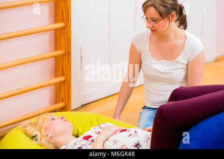 Midwife giving prenatal care for pregnant mother - Stock Photo
