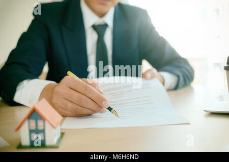 Businessman present contact of house insurance contract to purchase a home with a real estate agent. - Stock Photo