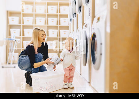Mom and baby in the laundry take things and play fun games - Stock Photo