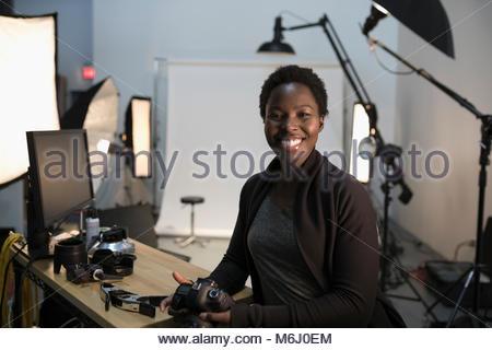 Portrait confident, enthusiastic female photographer preparing for photo shoot in studio - Stock Photo