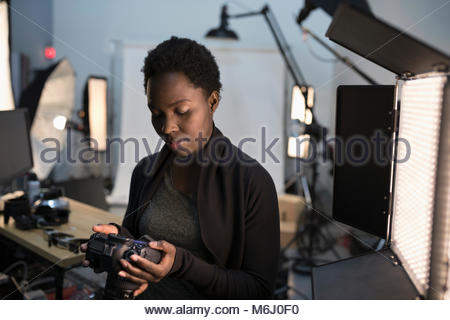 Female photographer looking at digital camera viewfinder at photo shoot in studio - Stock Photo