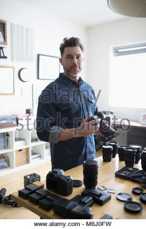 Portrait confident male photographer with digital camera and equipment - Stock Photo