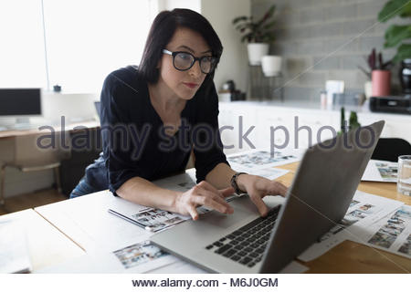 Female photo editor working at laptop, reviewing photo proofs in office - Stock Photo