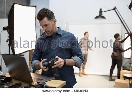 Male photographer with digital camera using laptop at photo shoot in studio - Stock Photo