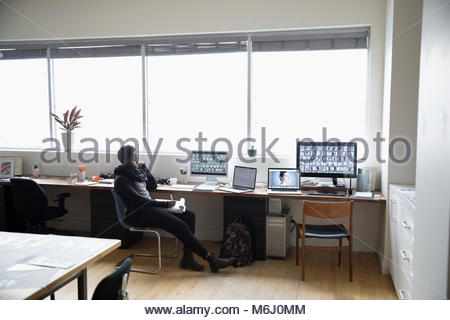 Female photo editor working at computer in office - Stock Photo