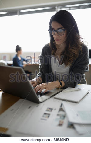 Female photo editor working at laptop in office - Stock Photo