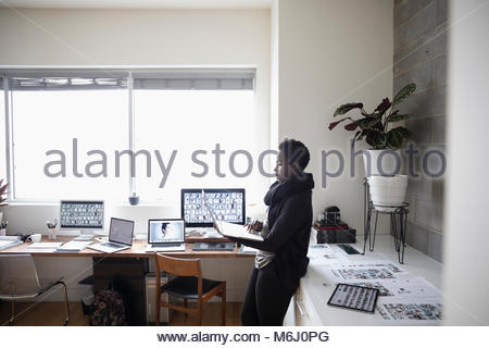 Female photo editor using laptop in office - Stock Photo