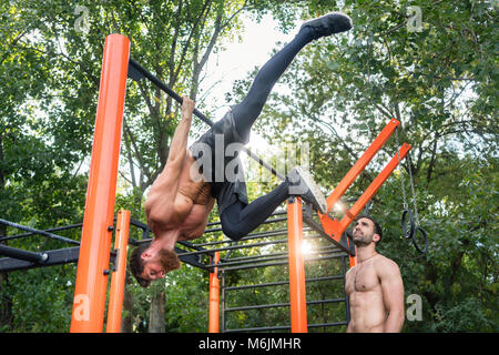 Shirtless bodybuilder hanging on horizontal bar during workout - Stock Photo