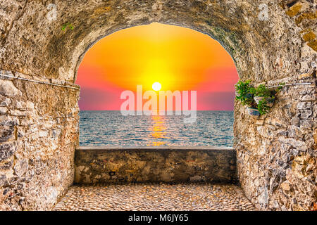 Scenic rock arch balcony overlooking a beautiful sunset on the mediterranean sea - Stock Photo