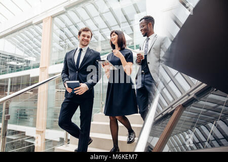 Three multiracial business people walking down on stairs with digital tablet - Stock Photo