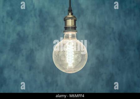 Decorative antique edison style light bulb against blue background. - Stock Photo