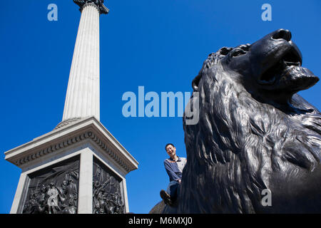 A tourist sits on top of one of the lion statues at the base of Nelsons column in the capital of the UK, London. - Stock Photo