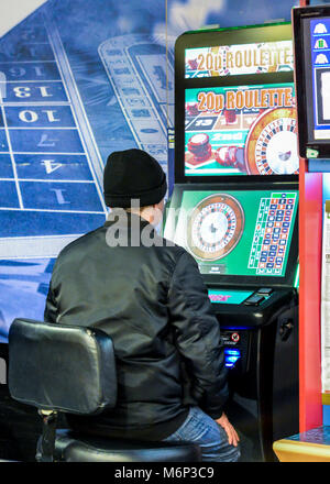 Mature man using fixed odds Roulette machine in Bookmakers. London, England, UK. Machine described as the Crack - Stock Photo