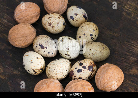 quail eggs and walnuts on a wooden texture as background - Stock Photo
