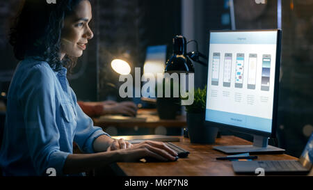 Beautiful Female Mobile Video Gaming Application Developer Works at Her Desk on a Personal Computer. In the Background - Stock Photo