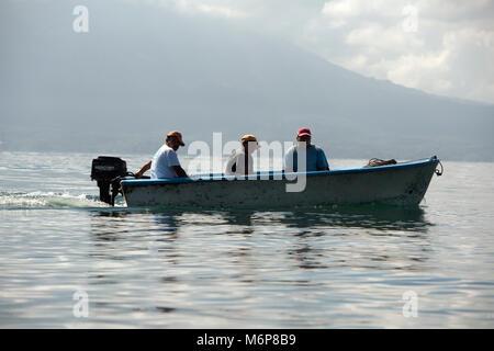 Indigenous, ethnic Maya men travelling by boat on Lake Atitlan. Lake Atitlán, Sololá Department, Guatemala. - Stock Photo