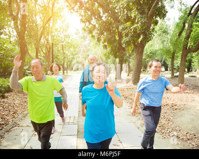 happy senior Group Walking In Park - Stock Photo