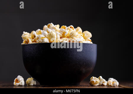 Popcorn in a ceramic bowl on a wooden background. - Stock Photo