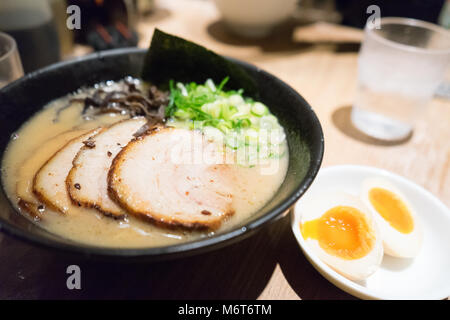 Traditional Japanese soup ramen with meat broth, asian noodles, seaweed, sliced pork, eggs and pickled ginger. Background. - Stock Photo
