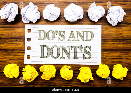 Handwritten text showing Do s And Do Not Donts. Business concept for Guide Allowed Written on sticky, wooden with - Stock Photo