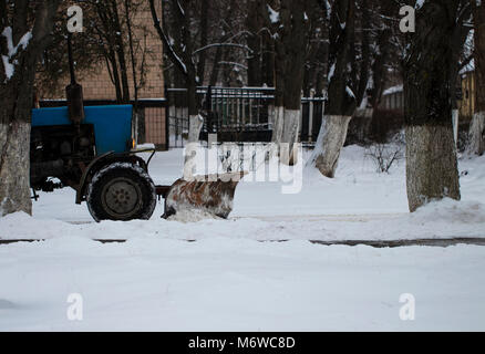 Snow plow removing snow from city road. - Stock Photo
