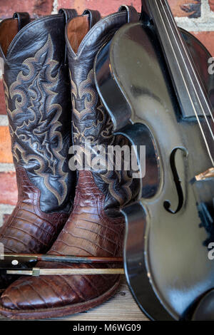 Well-worn cowboy boots and fiddle, Nashville, Tennessee, USA - Stock Photo