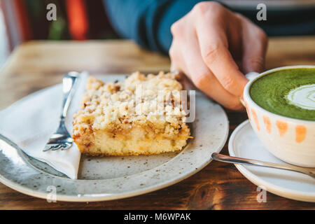Close-up man's hand holding mug of green tea with beautiful pattern in the form of white foam next to dessert - Stock Photo